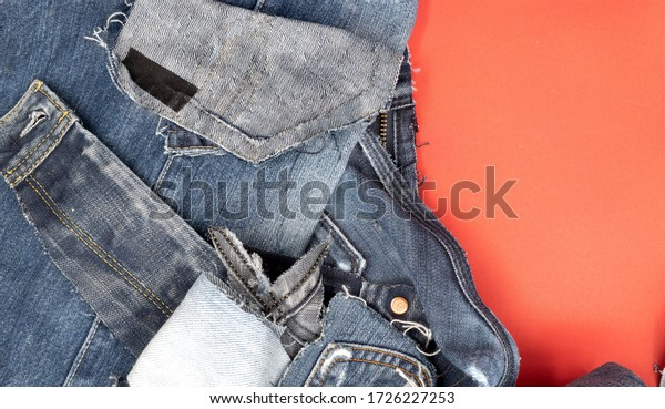 Pile of old blue jeans ready to be recycled. Flat lay with copy space in the red background.