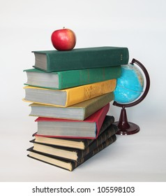 Pile of old books with apple on top and globe on white as a symbol of study and knowledge.