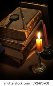 Pile of the old books and a candle