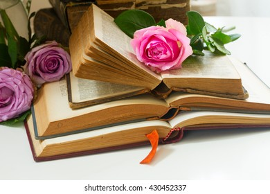 Pile of old books with fresh pink roses
