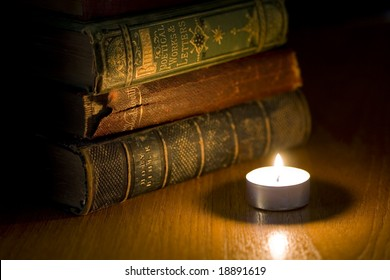 a pile of old books next to a small candle