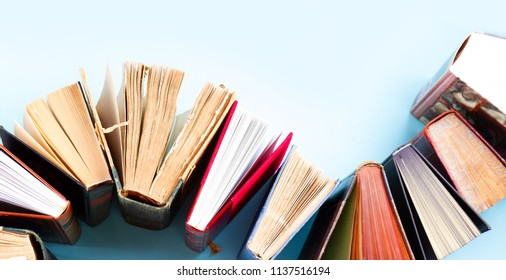 Pile of old books on blue background with copy space