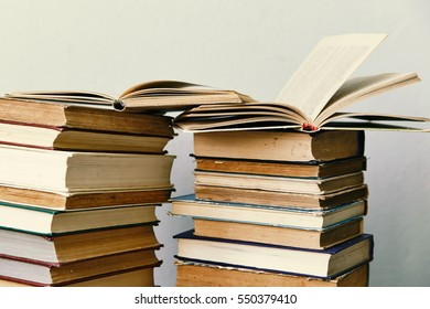 pile of old books and an open book  in hardcover
