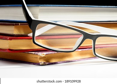 A pile of old books to read using glasses