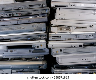 A pile of old, broken, and dusty laptops in a pile for recycling. They are dirty, and many are missing pieces. Focus point is the VGA port on the laptop in the middle.