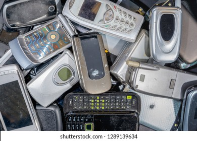 A pile of old cell phones to be recycled. There are a variety of phones, but most are the flip to open type. The phones are dirty. Branding was removed.