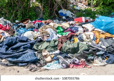 Pile of old clothes and shoes dumped on the grass as junk and garbage, littering and polluting the environment