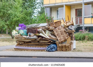 pile of old furniture and household goods on the roadside
