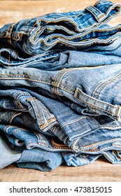 Pile of Old Indigo Jeans Denim on Wooden Table