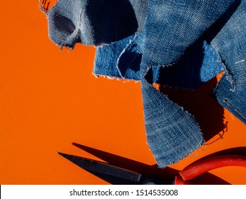 Pile of old jeans ready to be recycled for the circular economy. Industry scissors on an orange background. Room for copy. Bright light on a sunny day. Top view.