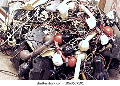 A pile of old landline telephones with tangled leads