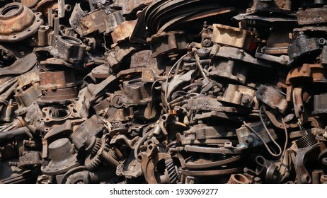 Pile of old machine parts in second hand machinery shop, background of damage and rusty old car machine