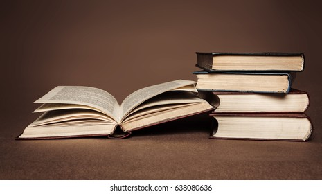 A pile of old open books on a brown background.