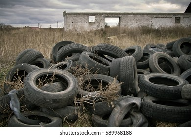 A pile of old rotten rubber tires on the ruined building background