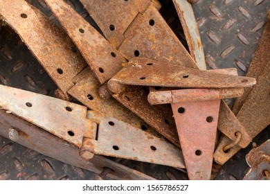 Pile of old rusty hinges on weathered diamond plate.