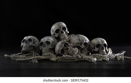 Pile of old skulls and bone put on dark background which has dim light  / Still life image, select focus, space for text