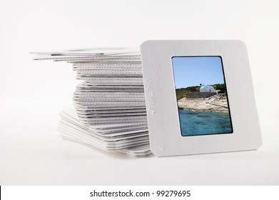 A pile of old slide photographs, with a photograph of a Greek island church