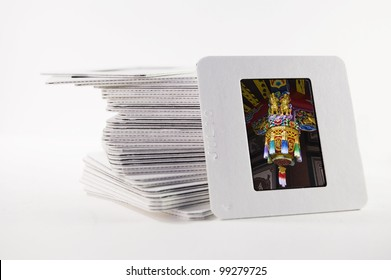 A pile of old slide photographs, with a photograph of a Chinese temple decoration