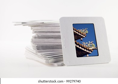 A pile of old slide photographs, with a photograph of a chinese temple roof