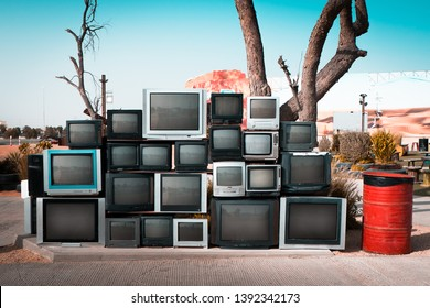 Pile of old televisions displayed along the road