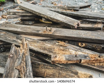 Pile of old wood ruins, decaying nails caused by demolition, destruction and decomposition, ready to send for recycle.