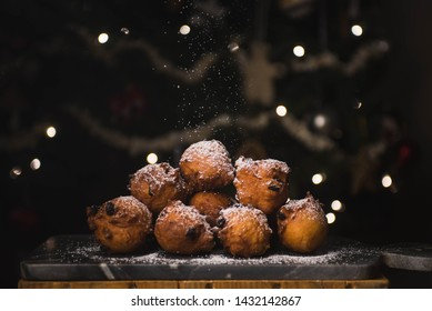 A pile of oliebollen is dusted with powdered sugar as it sits in front of an illuminated Christmas tree.