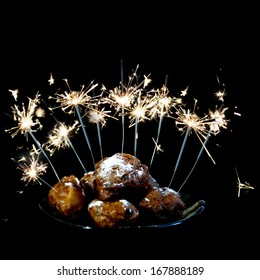 a pile with oliebollen with fireworks on a plate on a white background