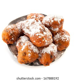 a pile with oliebollen on a plate on a white background