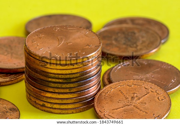 Pile of Omani 10 baiza bronze coins on a yellow background
