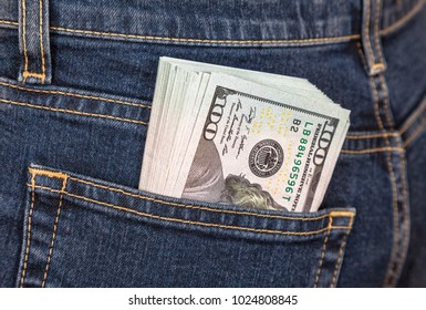 Pile of one hundred american dollar banknotes in the back jeans pocket