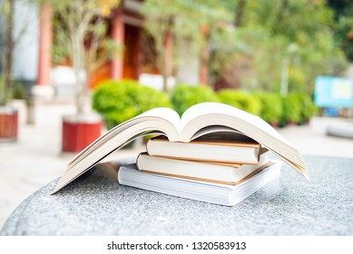 A pile of open books on a garden stone table