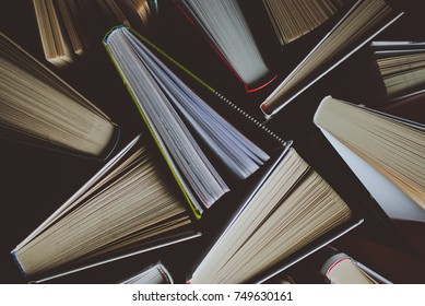 Pile of open books on the wooden table. Closeup of pages. Abstract concept of knowledge, education, learning, and literature.