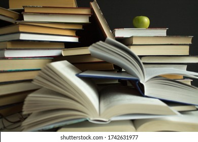 A pile of open and closed books scattered haphazardly on the table and an apple fruit