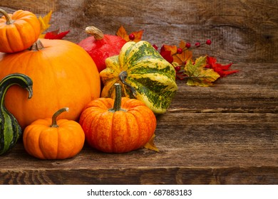 pile of orange and green pumpkins on wooden textured rustic table with copy space