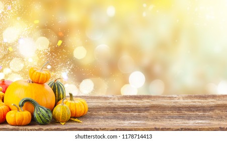 pile of orange harvest pumpkins with fall leaves on wooden table over fall background banner