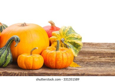 pile of  orange pumpkins with fall leaves on wooden  table isolated on white background