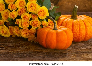 pile of orange pumpkins with yellow roses on wooden textured table