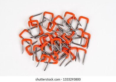 Pile of Orange PVC Insulated Electrical Wire Safety Staples on white background. Staples are used to hold cable in place.