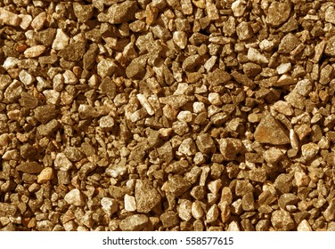 Pile of orange toned gravel stones. Abstract natural background and texture for design.