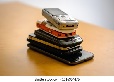 Pile of outdated Phones and Smartphones on a Table