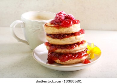 Pile of pancakes with raspberry jam on plate