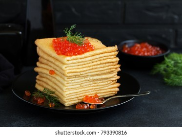 A pile of pancakes in Russian style with red caviar. .