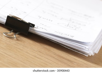 Pile of paper with clip close-up on wooden desk.