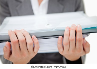 Pile of paperwork being held by female hands against a white background