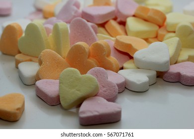 a pile of pastel colored candy hearts