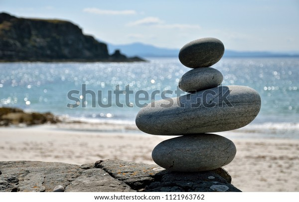 Pile of pebbles with a beautiful sandy beach in the background.