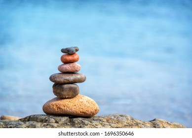 Pile of pebbles on a beach, blue water background