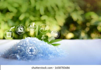 A Pile of PET bottle flakes with green tree blur background.Recycle icon,picking up Plastic Bottle,PET icon&Compress bale icon.Save environment concept