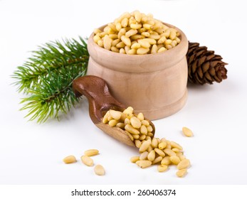 Pile of pine nuts with wooden scoop on white
