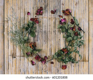 Pile of pink dried roses on rustic bamboo background as border. Top view point. Copy space